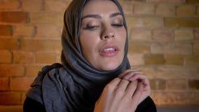 Close-upportret van volwassen aantrekkelijk moslimwijfje in hijab die camera bekijken en gelukkig binnen in comfortabel glimlache stock video