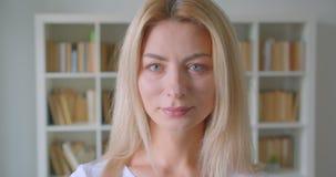 Close-upportret van volwassen Kaukasisch blondewijfje die camera bekijken die cheerfully binnen in de bibliotheek glimlachen met stock footage