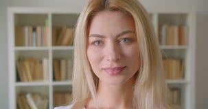Close-upportret van volwassen Kaukasisch blondewijfje die camera bekijken die gelukkig binnen in de bibliotheek glimlachen stock video