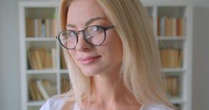 Close-upportret van volwassen Kaukasisch blondewijfje die in glazen camera bekijken die cheerfully binnen in de bibliotheek gliml stock videobeelden