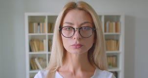 Close-upportret van volwassen Kaukasisch blondewijfje die in glazen camera binnen in de bibliotheek bekijken stock video