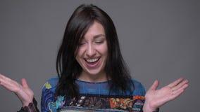 Close-upportret van volwassen Kaukasisch donkerbruin wijfje en het vieren het bekijken die camera met achtergrond worden opgewekt stock video
