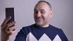 Close-upportret van volwassen Kaukasisch mannetje die het video callb spreken hebben en cheerfully glimlachen stock videobeelden