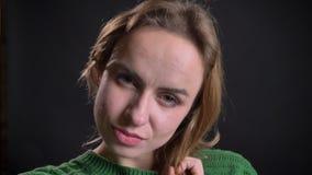 Close-upportret van volwassen Kaukasisch wijfje die en camera bekijken die glimlachen stellen stock videobeelden