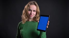 Close-upportret van volwassen Kaukasisch wijfje gebruikend de tablet en tonend het blauwe scherm aan camera het glimlachen stock videobeelden