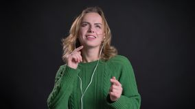 Close-upportret van volwassen Kaukasisch wijfje in vibes die en voor de camera luisteren dansen stock footage