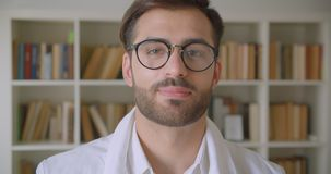 Close-upportret van volwassen knappe Kaukasische zakenman die in glazen camera in de bibliotheek met boekenrekken bekijkt stock video