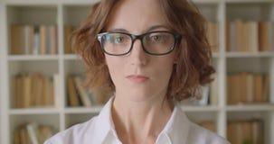 Close-upportret van volwassen roodharige aantrekkelijke Kaukasische onderneemster die in glazen camera binnen in bibliotheek beki stock footage