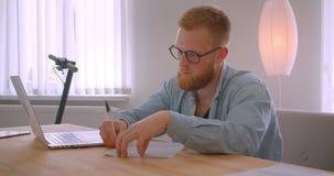 Close-upportret van volwassen roodharige Kaukasische zakenman die in glazen het document binnen in het bureau ondertekenen stock video
