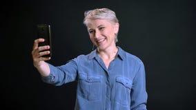 Close-upportret van volwassen vrolijk Kaukasisch wijfje met kort selfies op de telefoon maken en blondehaar die binnen glimlachen royalty-vrije stock foto's