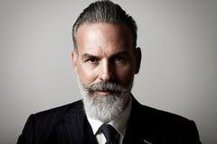 Close-upportret van volwassen zakenman die in kostuum dragen tegen de lege muur horizontaal royalty-vrije stock fotografie
