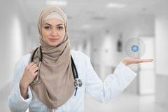 Close-upportret van vriendschappelijke, glimlachende zekere Moslim vrouwelijke arts die medische symbolen houden royalty-vrije stock foto's