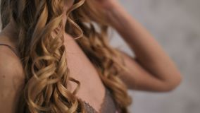 Close-upportret van vrouw die blond haar krullen stock video