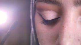 Close-upportret van vrouwelijke handen die samenstelling doen die mascara voor aantrekkelijke moslimvrouw in hijab op verstralers stock videobeelden