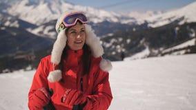 Close-upportret van vrouwelijke skiër bij de toevlucht van de bergski Gelukkige Vrouw in skikostuum en skibeschermende brillen di stock footage