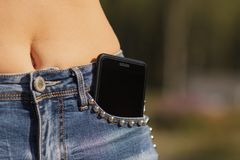 Close-upportret van Zwarte smartphone vooraan zak van meisjes` s jeans stock afbeelding