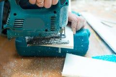 Close-upproces om paneel met figuurzaag te snijden Stock Fotografie