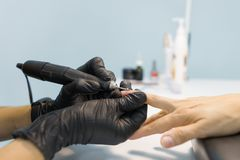 Close-upproces van professionele manicure De manicurevrouw dient zwarte handschoenen in makend manicure gebruikend professionele  stock fotografie