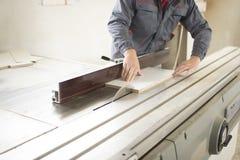 Close-upproces van timmermansarbeider met cirkelzaagmachine bij houten straal dwarsknipsel tijdens meubilairvervaardiging Stock Afbeelding