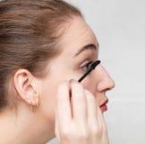 Close-upprofiel dat van jonge vrouw mascara op haar wimpers toepast stock afbeeldingen