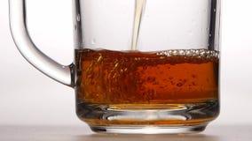 Close ups, jet of hot tea fills the glass cup stock video