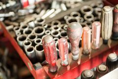 Closeup of wrench sockets of various sizes needed for car repair. Close-ups with various sizes of sockets and various repair tools arranged in red Royalty Free Stock Photos