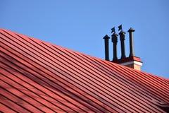 Close-upschoorstenen op het rode dak en de hemel stock fotografie
