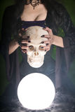 Close-upschot van een heks die met lange spijkers menselijke schedel houden stock foto