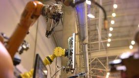 Close-upschot van het bewegen van door buizen geleid automatisch robotachtig wapen in proces op tentoonstellingsachtergrond stock videobeelden