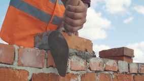 Close-upschot van Metselaar gezette baksteen op de muur stock videobeelden