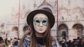 Close-upschot van vrouw met lang haar in traditioneel Carnaval-masker die zich bij de vierkante langzame motie van Venetië bevind stock video
