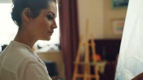 Close-upschot van vrouwelijke kunstenaar die mooi beeld schilderen die tot meesterwerk leiden die geconcentreerde olieverven op p stock video