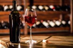 Close-upschot van wijnfles en glas op een houten lijst wordt geplaatst die Planken met wijnflessen op de achtergrond Royalty-vrije Stock Afbeelding