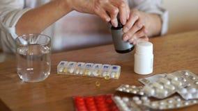 Close-upsportret van het wapen die van een bejaarde aan artritis lijden die een dagelijkse dosis drugs en vitaminen nemen stock footage