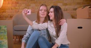 Close-upspruit die van jonge mooie lesbische paarbloggers bij camera stromen spreken levend op telefoon het koesteren en stock footage