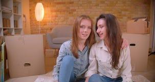 Close-upspruit die van jonge mooie lesbische paarbloggers op camera spreken die en op de vloer in a onlangs koesteren zitten stock videobeelden