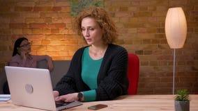 Close-upspruit die van jonge onderneemster aan laptop werken die een telefoongesprek hebben en binnen in het bureau ontspannen stock video
