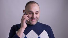 Close-upspruit van de Kaukasische mens die op middelbare leeftijd een toevallig gesprek op de telefoon hebben die cheerfully lach stock videobeelden