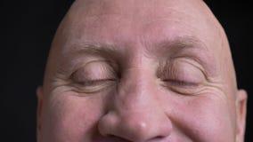 Close-upspruit van de Kaukasische mens die op middelbare leeftijd zijn ogen openen die recht en gezichts camera met opwinding bek stock footage