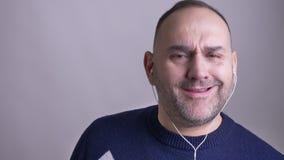 Close-upspruit van de midden oude Kaukasische aan muziek in vibes luisteren en mens die cheerfully zingen stock videobeelden