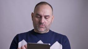 Close-upspruit van de midden oude Kaukasische mens die op tablet toen lookinga bij camera en het glimlachen doorbladeren stock video