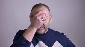 Close-upspruit van de volwassen Kaukasische mens die zijn hoofd met een hand die slaan en onhandig voor de camera worden geverwar stock video
