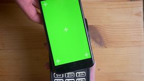 Close-upspruit van een betalingsterminal die voor betaling door een reclame op de telefoon met het groene chroma-zeer belangrijke stock footage