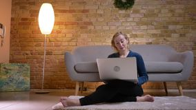 Close-upspruit van eldery Kaukasisch wijfje die op een film op laptop met opwinding letten terwijl het zitten op de vloer stock video