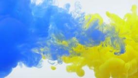 Close-upspruit van gele en blauwe waterverfinkt die en in vloeistof bespatten drijven stock illustratie