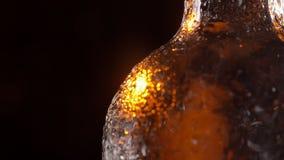 Close-upspruit van glanzende bierfles met het koude dauw dalen van het die rond in motie spinnen stock video