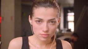 Close-upspruit van het jonge aantrekkelijke atleet vrouwelijke puttting op haar vibes die camera in de gymnastiek binnen bekijken stock footage