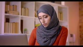 Close-upspruit van het jonge aantrekkelijke moslim vrouwelijke werknemer typen op aan camera draaien en gelukkig laptop die gliml stock videobeelden