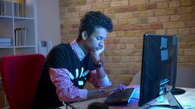 Close-upspruit van het jonge Indische aantrekkelijke mannelijke typen op de laptop zitting binnen in de comfortabele flat met neo stock videobeelden