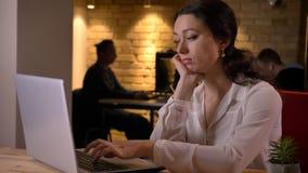 Close-upspruit van het jonge sadfemalewerknemer typen op laptop en het zijn ongelukkig binnen op de werkplaats royalty-vrije stock afbeelding